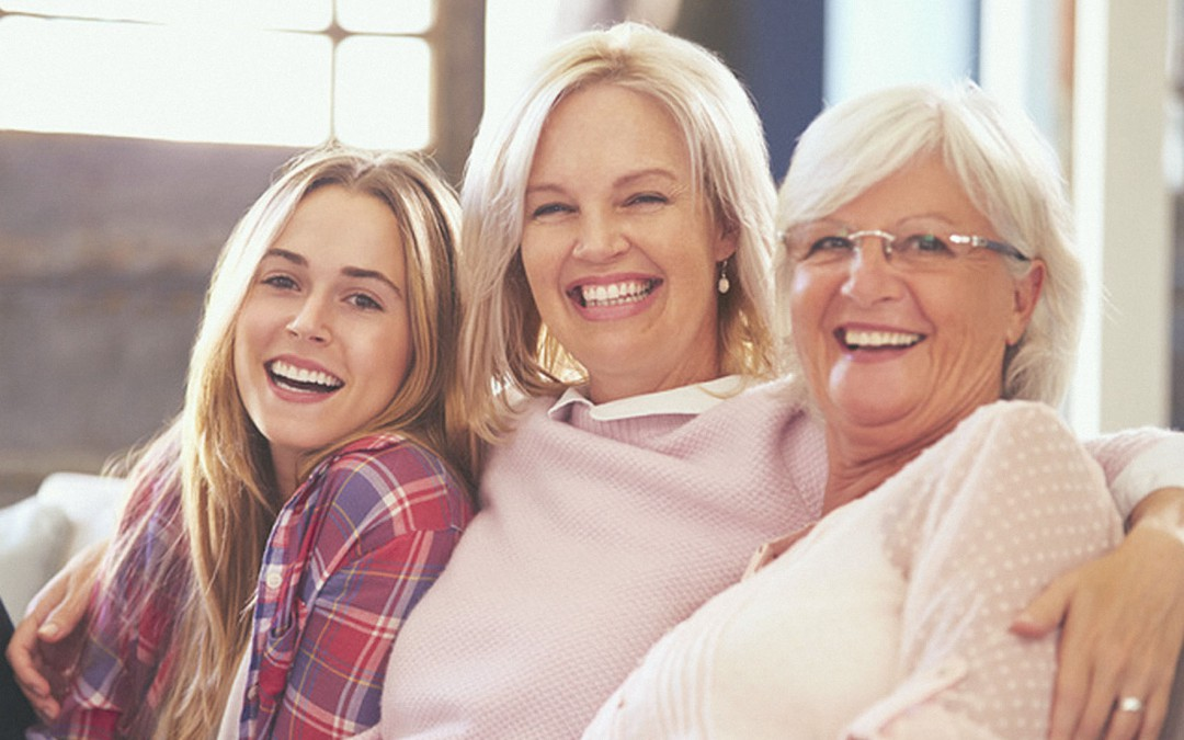 Three female generations sit on a couch smiling