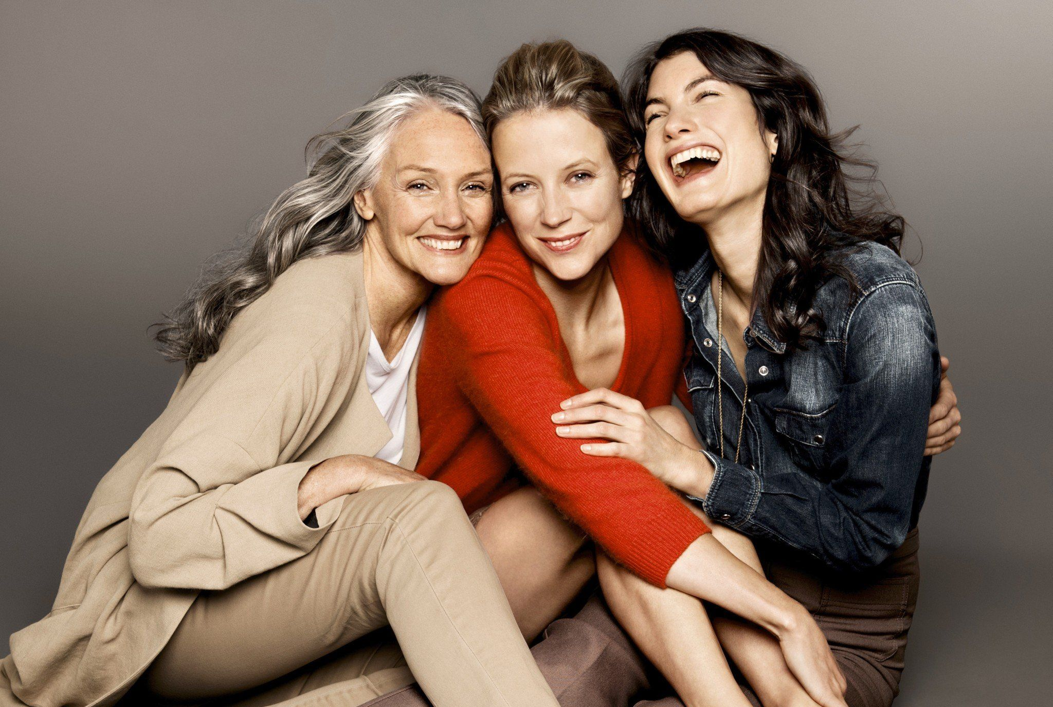 three happy women of all ages sitting together