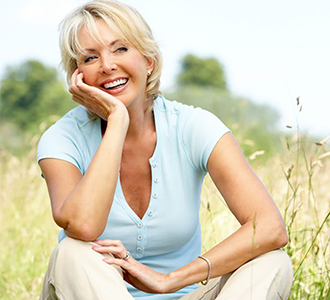 Woman sitting in field smiling