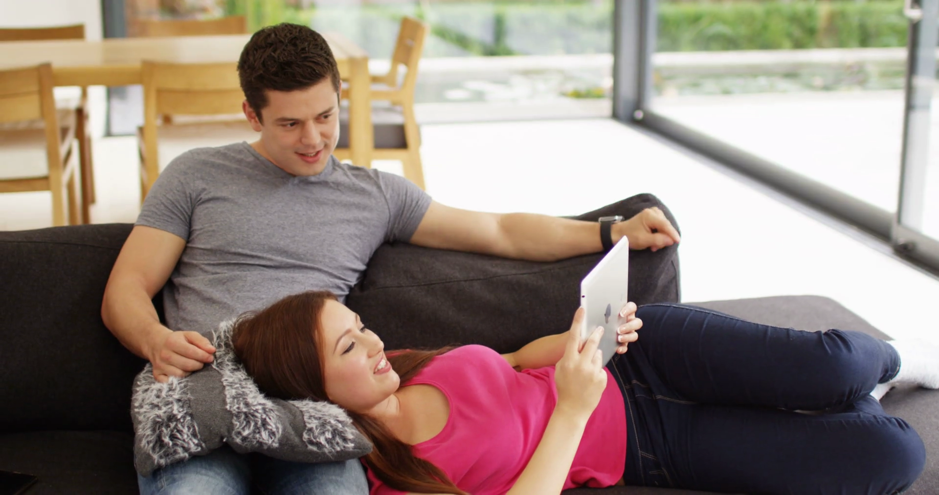 Young couple sitting on cough looking at Ipad