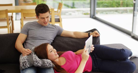 Couple-on-Couch-looking-at-iPad
