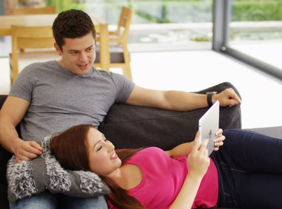Young-Couple-Sittingon-Couch-looking-at-iPad-planning-a-family